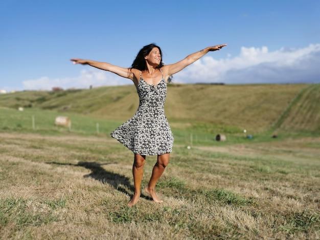 幸せな魅力的なブルネットの女性が田舎で日没時に踊る
