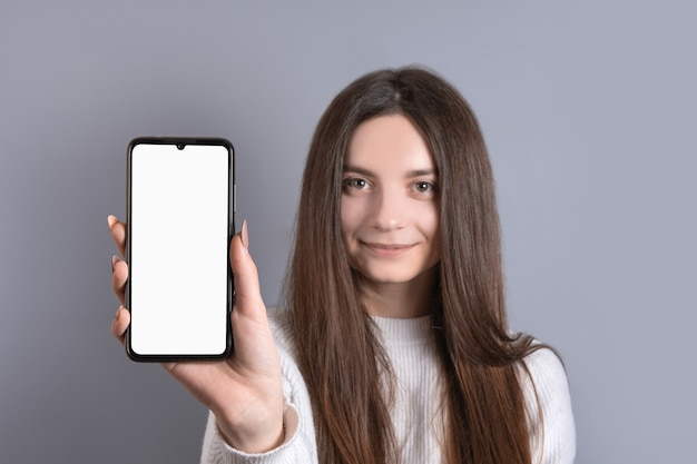 Happy attractive brunette woman girl in sweater showing hold blank phone smartphone screen. looking at the camera and smile over gray background.
