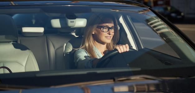 안경을 쓴 매력적인 백인 여성 사업가가 도시를 가로질러 현대적인 차를 몰고 있다