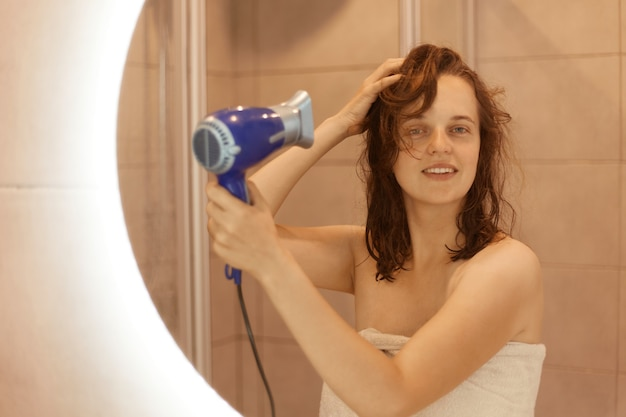 Happy attractive caucasian joyful dark haired woman in bath towel drying hair with hair dryer in bathroom after shower at home, looking at her reflection in mirror.