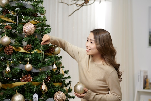 木の上にガラスのつまらない飾りを保持している幸せな魅力的な中国の女性。