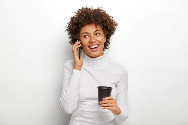 Happy attractive dark skinned model talks with operator about mobile phone benefits