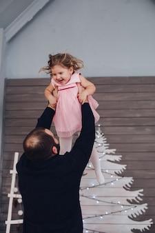 幸せな魅力的な父は彼の腕に抱き、新年の雰囲気の中で彼の小さなかわいい娘の家を楽しんでいます