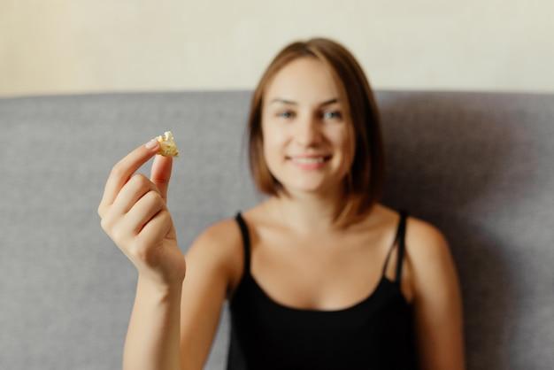 灰色のソファーに座っていたポップコーンを持って幸せな魅力的な女の子。