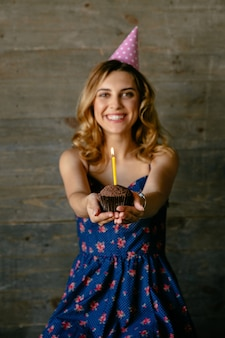 Happy attractive girl holds a chocolate cupcake with candle, celebrating her birthday