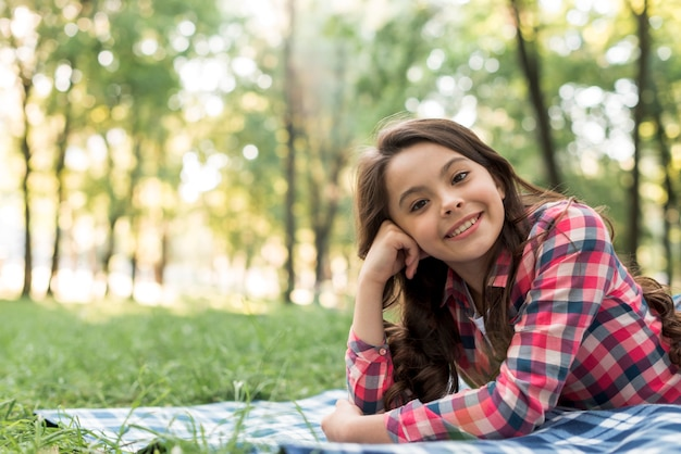 Happy attractive girl looking at camera lying in park