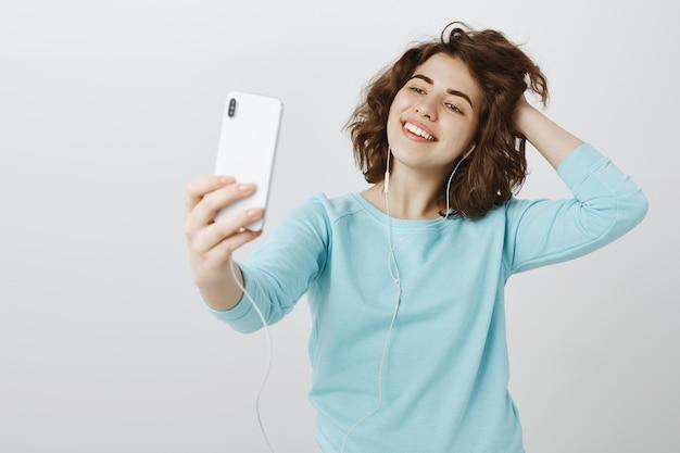Счастливая привлекательная девушка, делающая селфи на смартфоне, позирует с наушниками