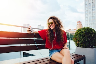 Happy attractive girl with curly hair, in earphones, looks at smartphone screen