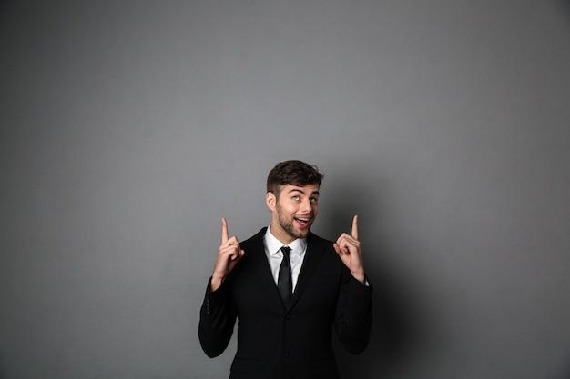 2本の指で上向きに指している黒のスーツで幸せな魅力的な男