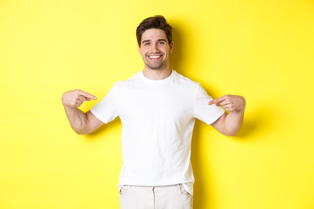 Happy attractive guy pointing fingers at your logo, showing promo on his t-shirt, standing over yellow background.