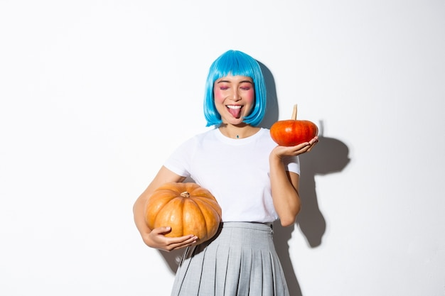Happy attractive japanese girl in blue party wig, close eyes and showing tongue joyfully, celebrating halloween, holding two pumpkins.