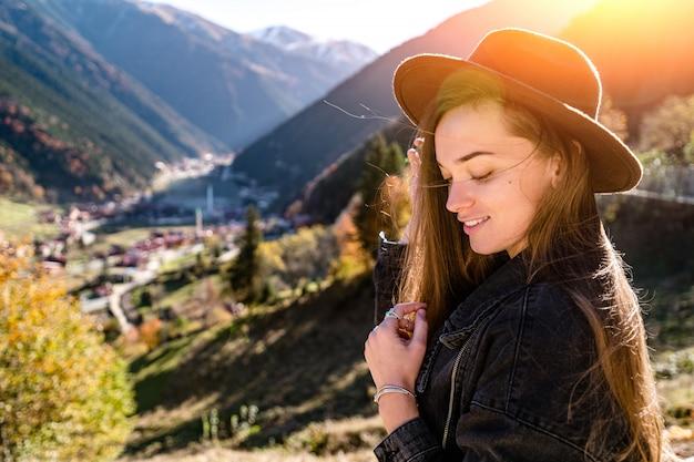 トルコ旅行中に山とトラブゾンのウズンゴル湖に立っているフェルト帽子と黒いデニムジャケットで幸せな魅力的なうれしそうな女性旅行者