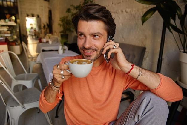 Счастливый привлекательный мужчина с бородой пьет кофе во время разговора по мобильному телефону, позирует над интерьером кафе, находится в хорошем настроении