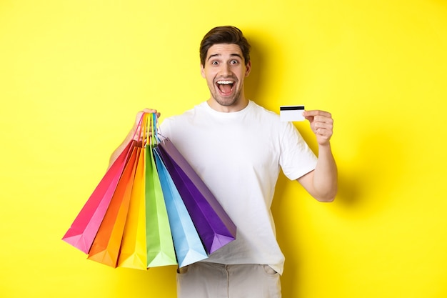 Happy attractive man holding shopping bags, showing credit card, standing over yellow wall