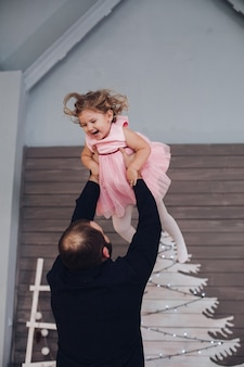 Happy attractive man holds in his arms and has fun with little cute girl in the new year atmosphere