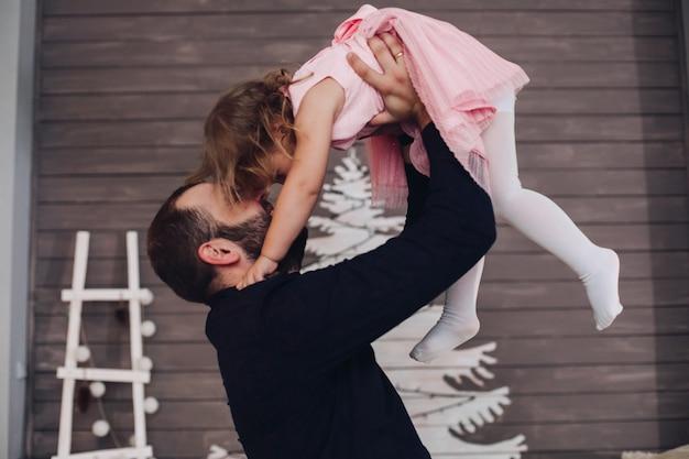 Un uomo felice e attraente tiene tra le sue braccia e si diverte con una bambina carina nell'atmosfera del nuovo anno