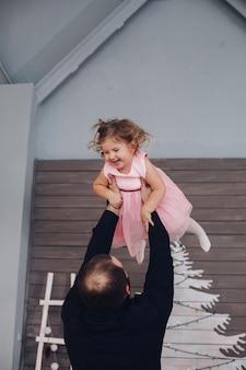 幸せな魅力的な男は彼の腕を保持し、新年の雰囲気の中で小さなかわいい女の子と楽しんでいます
