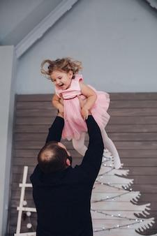 Счастливый привлекательный мужчина держит на руках и веселится с маленькой милой девочкой в новогодней атмосфере