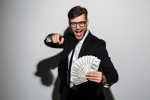 Счастливый привлекательный мужчина в очках и черном костюме держит кучу денег, указывая пальцем на вас