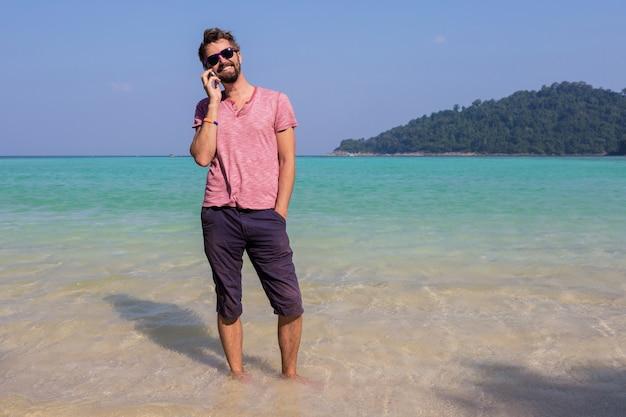 Uomo attraente felice in occhiali da sole alla moda con la barba utilizzando il telefono cellulare in spiaggia