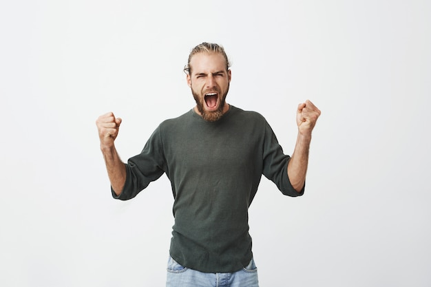 Happy attractive man with beard screaming loudly and expressive gesticulating with hands