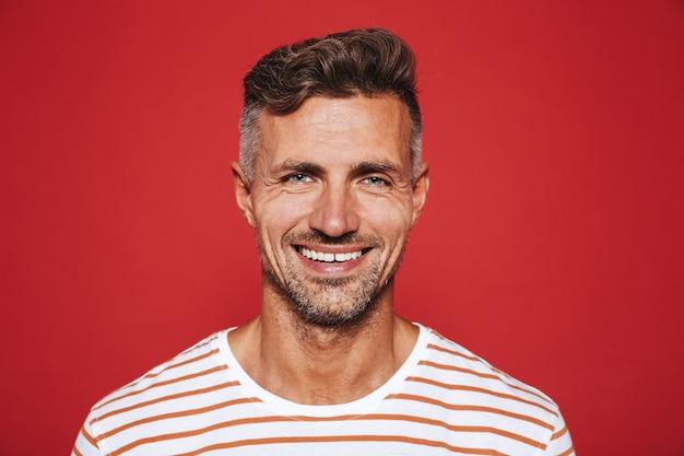 Счастливый привлекательный мужчина с щетиной в полосатой футболке улыбается изолированным на красном