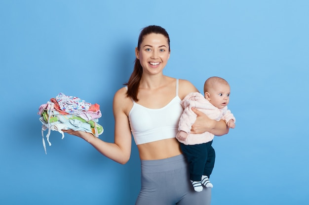 Happy attractive mother with baby isolated over blue background, lady with newborn daughter looks at camera with charming smile, holds stack of kids clothes, takes care of child during maternity leave