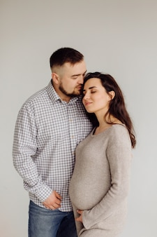Happy and attractive pregnant woman and her husband posing in studio