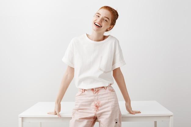 幸せな魅力的な赤毛の女性笑顔、無駄のないテーブル