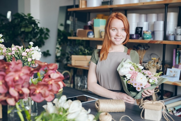 Happy attractive redhead young florist in apron holding beautiful bouquet while working in own shop