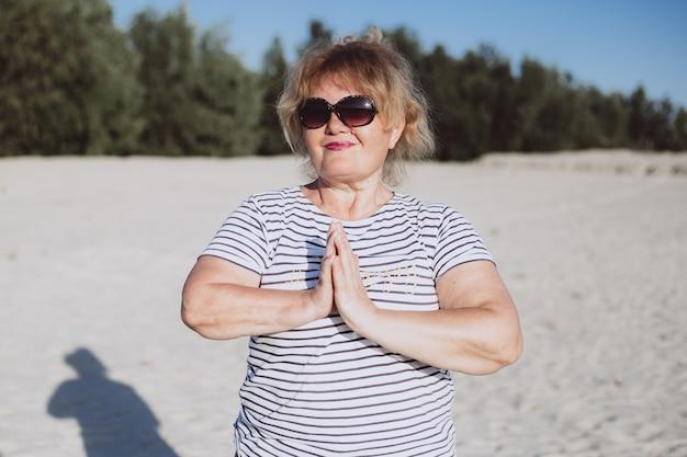Happy attractive senior woman in summer in beach