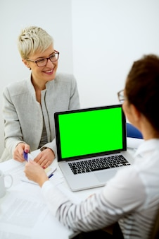 Happy attractive short hair middle aged woman with eyeglasses sitting in front of the financial manager and giving a bank card with a blank green editable screen on a laptop.