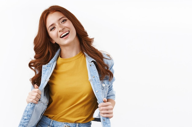 Felice attraente ed elegante donna rossa in giacca di jeans, che mostra t-shirt gialla, testa inclinata e sorride soddisfatta, sentendosi spensierata e gioiosa, muro bianco