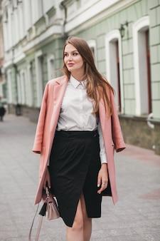 Счастливая привлекательная стильная улыбающаяся женщина гуляет по городской улице в розовом пальто весенней модной тенденции, элегантном стиле