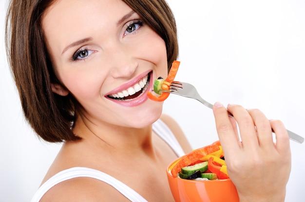 幸せな魅力的な女性が野菜サラダを食べる