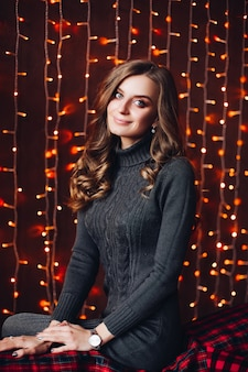 Happy attractive woman in gray knit dress against christmas lights.