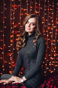 Счастливая привлекательная женщина в сером платье knit против светов рождества.