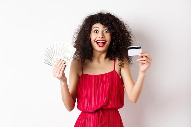 赤いドレスを着た幸せな魅力的な女性、喜びの叫びとお金でプラスチックのクレジットカードを表示し、賞を獲得し、白い背景の上に立っています。