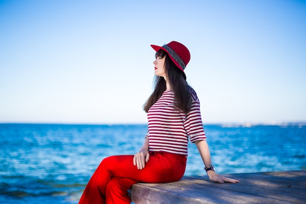 Happy attractive woman in red sitting over blue sea and sky