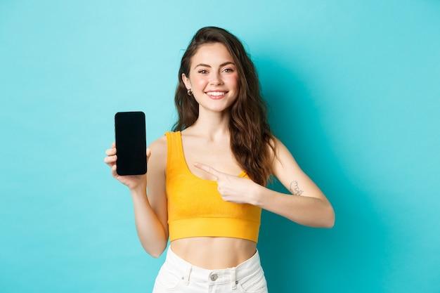 Счастливая привлекательная женщина, показывающая рекламу на экране смартфона, указывая на пустой дисплей телефона и улыбаясь, стоя на синем фоне.