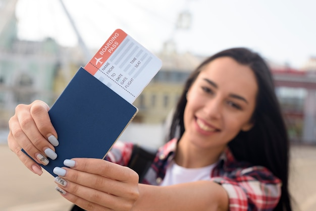 Happy attractive woman showing passport and air ticket at outdoors