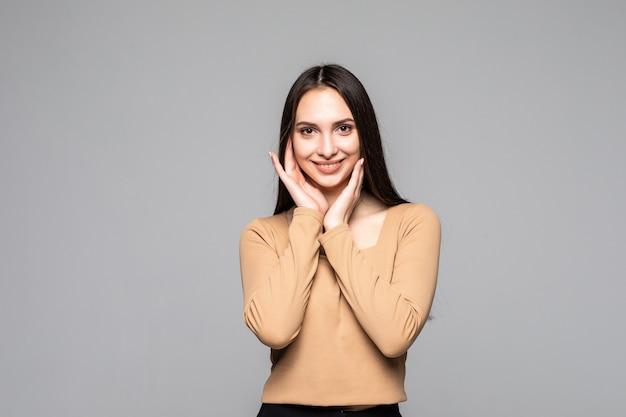 Счастливая привлекательная женщина, стоящая над серой стеной и смотрящая вперед