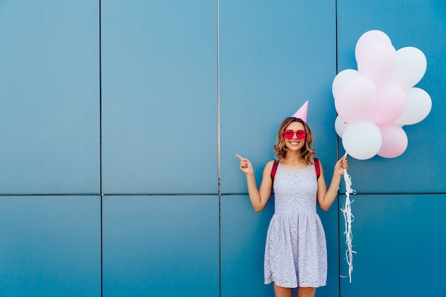 Happy attractive woman in sunglasses and party hat, holds air balloons