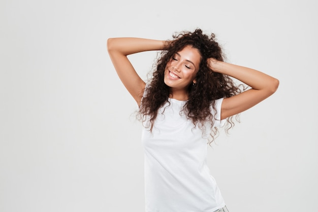 Happy attractive woman with eyes closed playing with her hair
