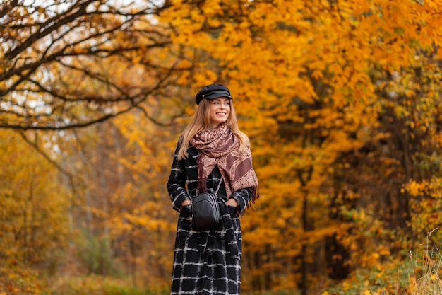 Счастливая привлекательная женщина с прекрасной улыбкой в спортивном синем стильном топе с современными беспроводными наушниками, бегом в лесу в яркий солнечный летний день. радостная девушка бежит и слушает музыку на закате