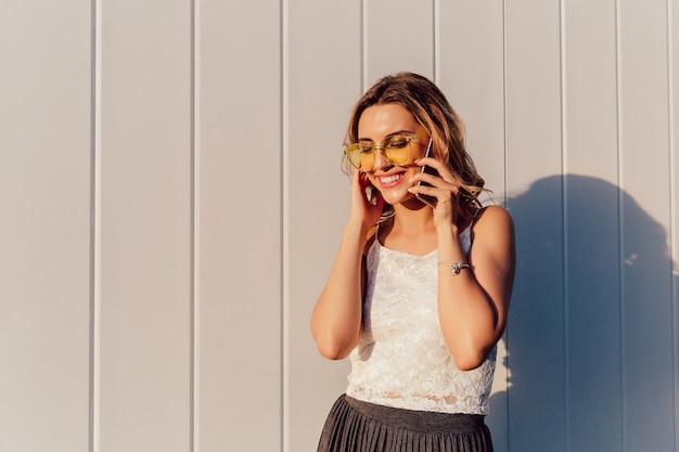 Happy attractive woman in yellow sunglasses having phone conversation