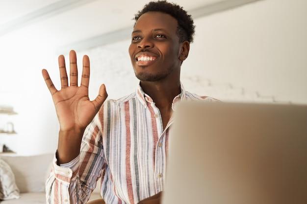 幸せで魅力的な若いアフロアメリカ人男性ブロガーが写真をアップロードし、ソーシャルネットワークに新しい投稿を入力し、カフェに座ってオンラインでフォロワーとチャットし、手を振って、広く笑っています。