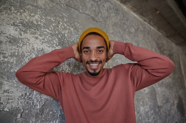 Happy attractive young bearded dark skinned male with charming smile looking cheerfully and holding his head with raised hands, being in high spirit while standing over concrete wall