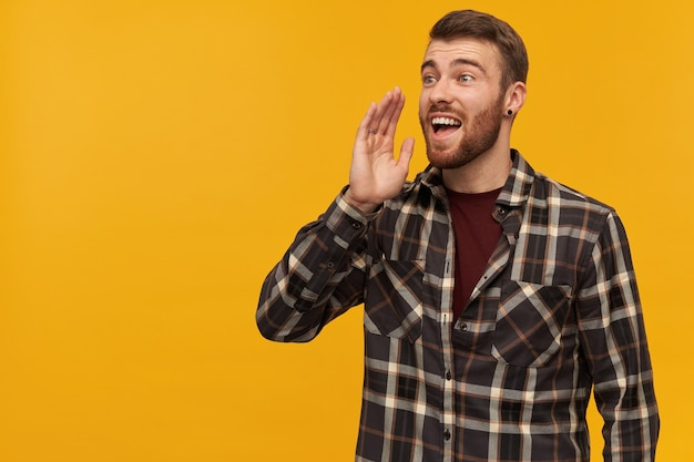 Happy attractive young bearded man in checkered shirt with hand near face shouting loudly and calling someone far away over yellow wall