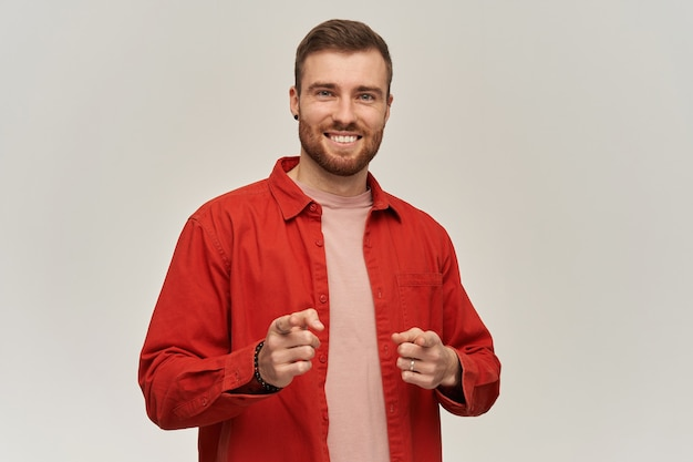 Happy attractive young bearded man in red shirt looks confident smiling and pointing on you at front over white wall